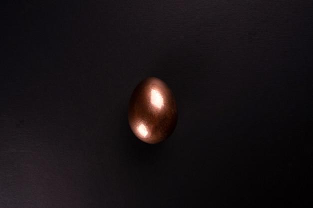 Jedno złote jajko leży na czarnym tle, minimalizm. leżał płasko, widok z góry, miejsce.