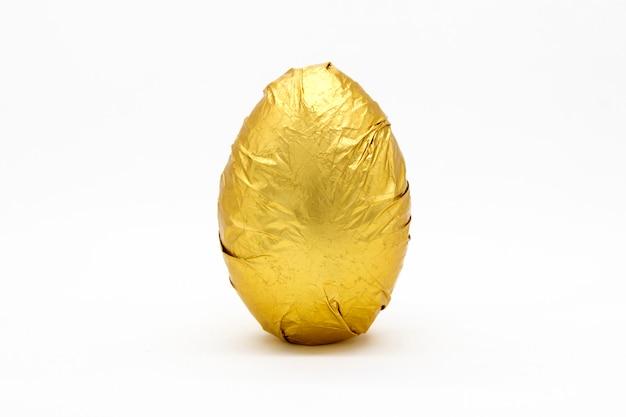 Jedno złote jajko w marszczonej metalicznej złotej folii na białym tle.