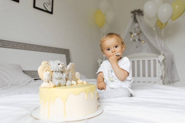 Jednoletni chłopiec degustujący tort urodzinowy w swoje urodziny
