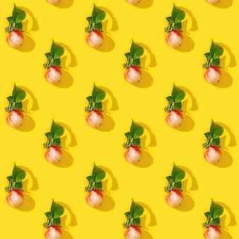 Jednolity, regularny, kreatywny wzór z małych czerwonych jabłek i zielonych liści