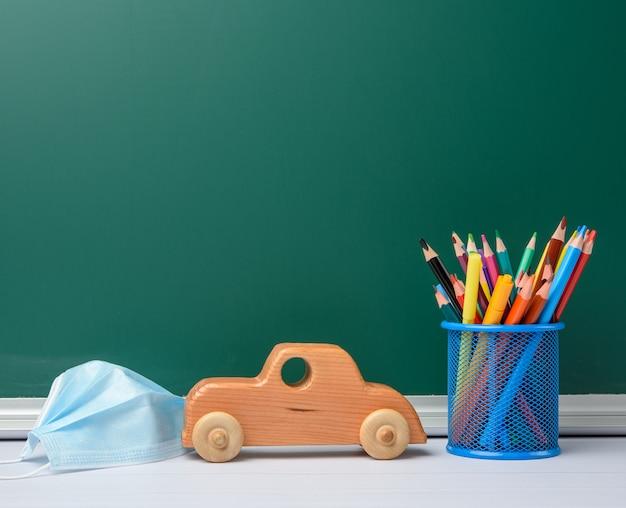Jednorazowa maska medyczna, przybory szkolne na tle zielonej tablicy kredowej, koncepcja kwarantanny szkolnej, miejsce na kopię