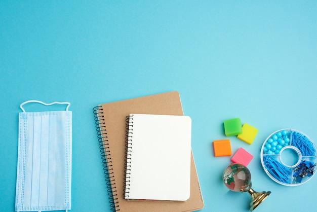 Jednorazowa medyczna maska na twarz i spiralny notatnik papierowy, artykuły papiernicze na niebieskim tle, koncepcja szkolenia w zakresie epidemii i pandemii, powrót do szkoły, miejsce na kopię