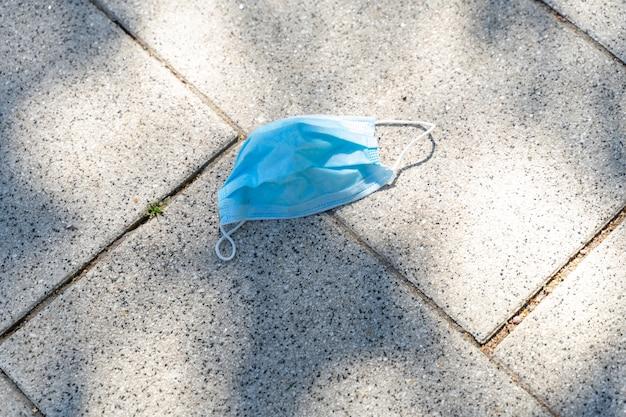 Jednorazowa niebieska maska na kamiennej ścieżce w parku. niewłaściwa utylizacja masek. zanieczyszczenie środowiska.