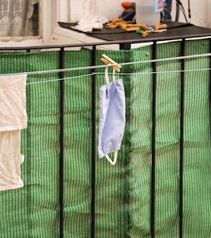 Jednorazowa ręcznie wykonana maska medyczna. wieszanie prania do wyschnięcia na balkonie w hiszpanii, bez masek