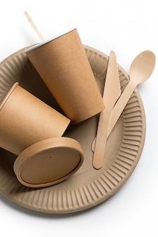 Jednorazowa zastawa stołowa wykonana z drewna bambusowego i papieru na białej powierzchni. zdjęcie jest pokryte ziarnistością i hałasem.