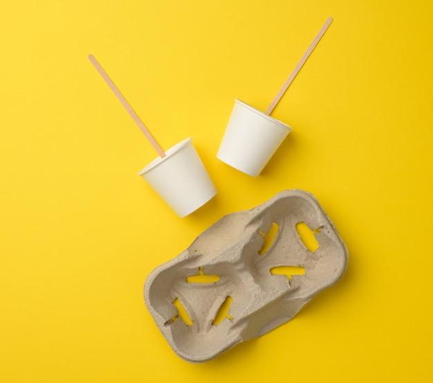 Jednorazowe białe papierowe kubki, drewniane patyczki i papierowa taca na żółtym tle. pojemnik na napoje na wynos