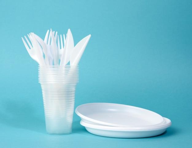 Jednorazowe białe plastikowe talerze stołowe, kubki, widelce i noże na niebieskim tle, zestaw piknikowy