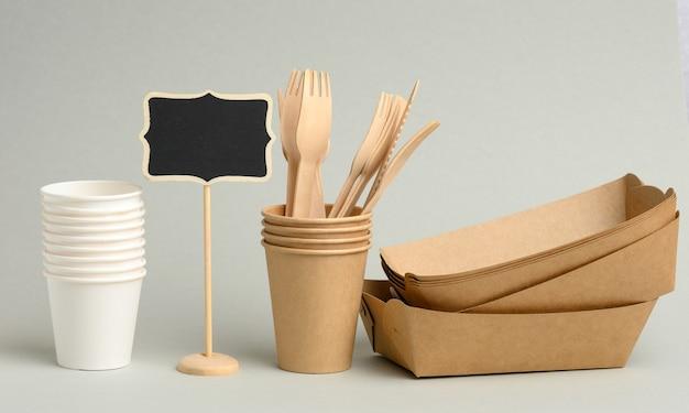 Jednorazowe brązowe, białe papierowe kubki, prostokątne talerzyki i drewniane widelce na szarej powierzchni. zero odpadów, bez plastiku