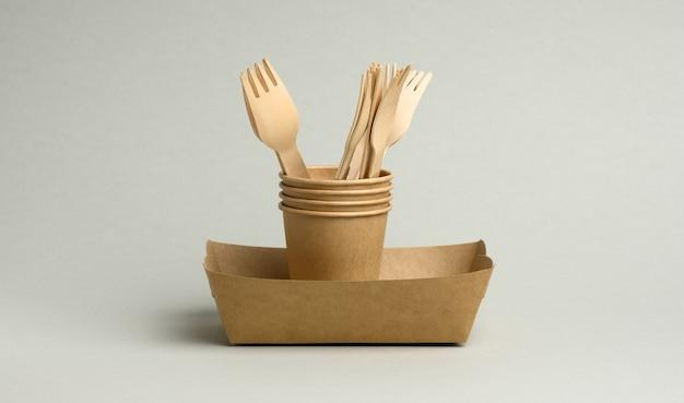 Jednorazowe brązowe papierowe kubki, prostokątne talerzyki i drewniane widelce na szarym tle. zero odpadów, bez plastiku