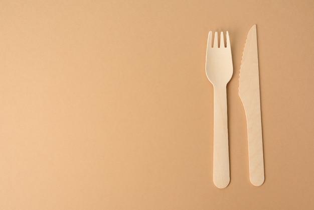 Jednorazowe drewniane widelce i nóż do fast foodów i pikników na brązowym tle, miejsce na kopię
