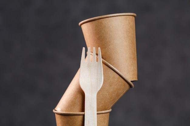 Jednorazowe kubki papierowe do napojów na ciemnym tle. naczynia na piknik eco. pusta filiżanka kawy z tobą
