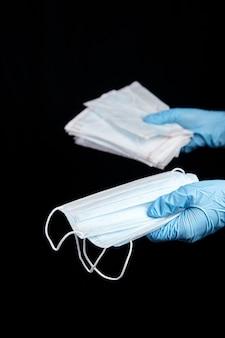 Jednorazowe maski na twarz w dłoni w niebieskiej rękawiczce, odizolowane na czarnym tle. medyczne maski chirurgiczne. covid-2019, pandemia koronawirusa. ochrona przed chorobami przenoszonymi drogą powietrzną