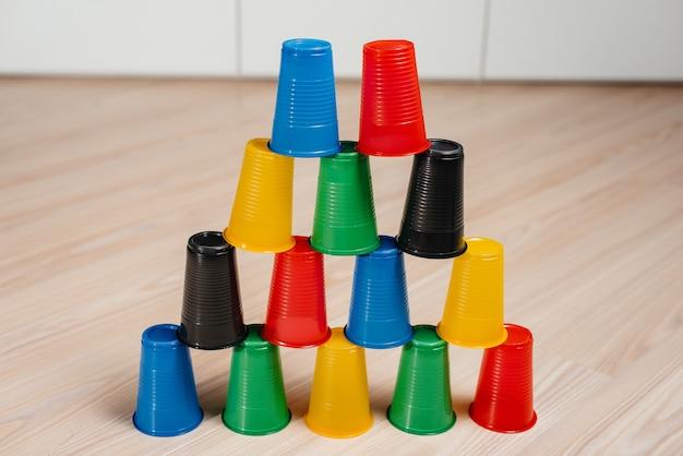 Jednorazowe plastikowe kubki ułożone są w piramidę. zanieczyszczenie środowiska odpadami ludzkimi.