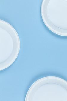 Jednorazowe plastikowe naczynia, talerze, niebieskie tło, miejsce