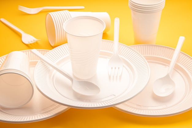 Jednorazowe plastikowe pojemniki na naczynia. grupa puste talerze, kubki, łyżki, widelce i naczynia na żółtym stole