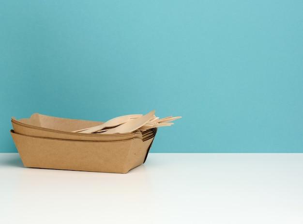 Jednorazowe prostokątne talerze papierowe, drewniane widelce i noże na białym stole, niebieskim tle