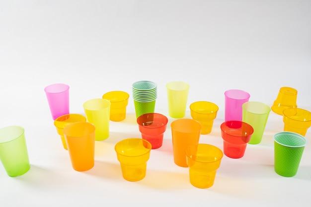 Jednorazowe przybory plastikowe. kolorowe kubki różnej wielkości wykonane z taniego plastiku używanego i zapomnianego