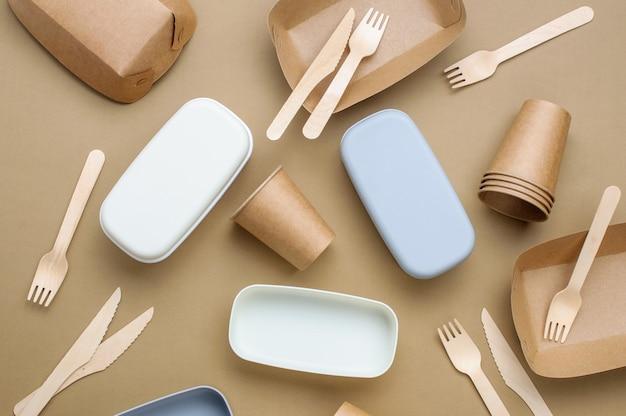 Jednorazowe, przyjazne dla środowiska opakowanie na żywność. brązowe pojemniki na żywność z papieru pakowego na beżowym tle. widok z góry, płaski układ.