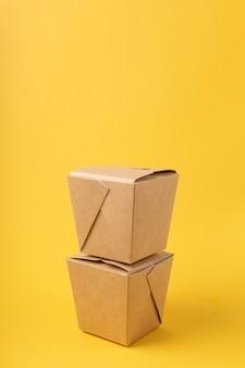 Jednorazowe pudełka do dostarczania żywności na żółtym tle