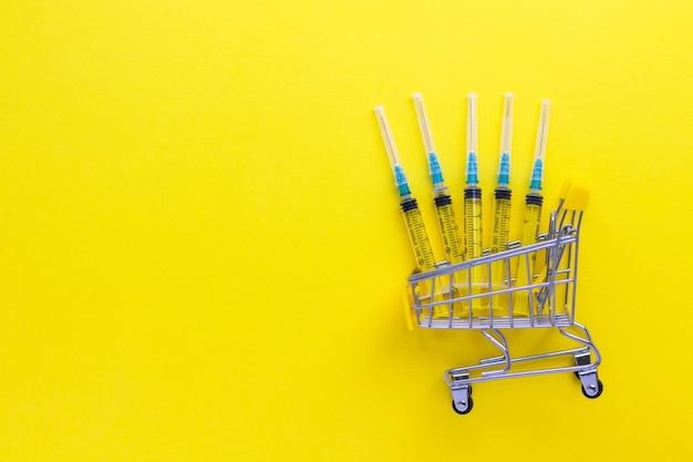 Jednorazowe strzykawki w mini koszyku na żółtym tle. pojęcie medyczne i opieki zdrowotnej. widok płaski świeckich, z góry z miejsca na kopię.