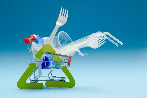 Jednorazowego użytku, jednorazowe zastawy stołowe i znak recyklingu na tle. łyżki, widelce