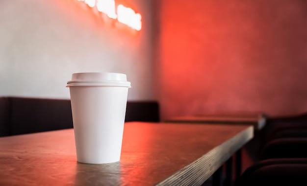 Jednorazowy biały papierowy kubek do kawy stoi na stole z neonem.