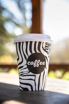 Jednorazowy kubek na wynos z kawą na drewnianej ławce w porannym ogrodzie