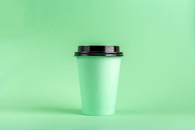 Jednorazowy kubek papierowy eco z kawą na zielonym tle. makieta do reklamy.