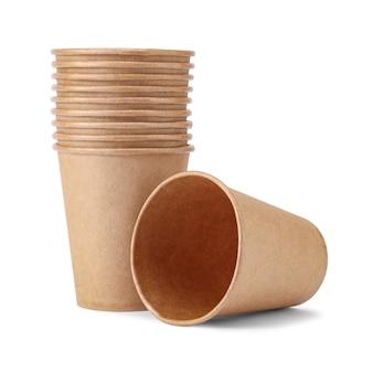 Jednorazowy kubek papierowy leży w pobliżu stosu kubków, na białym tle. ekologiczna jednorazowa zastawa stołowa z naturalnego materiału.