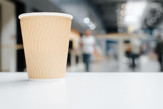 Jednorazowy papierowy kubek kawy stoi na białym stole w kawiarni, rozmycie tła jasnego miejsca publicznego, w pomieszczeniu. selektywne skupienie się na filiżance z napojami, kopia przestrzeń. widok z boku na poziomie obiektu.
