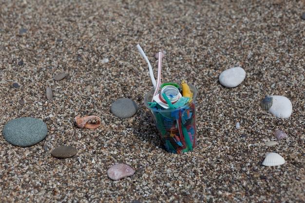 Jednorazowy plastikowy kubek z plastikowymi śmieciami na plaży selektywne skupienie
