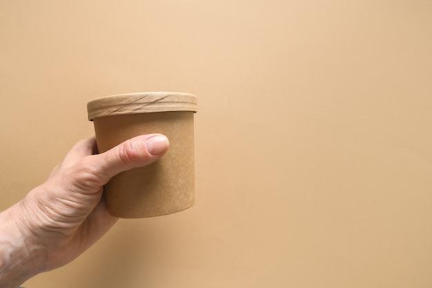 Jednorazowy tekturowy kubek do zupy w ręce womans na brązowym papierze z miejsca na kopię
