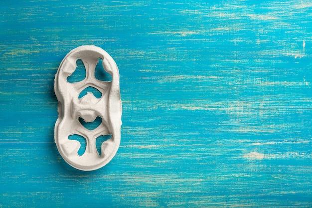 Jednorazowy uchwyt na kubek na niebieskiej drewnianej powierzchni