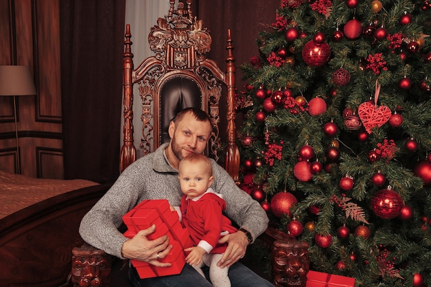 Jednoroczne dziecko o niebieskich oczach w stroju świątecznym z tatą w salonie z drzewem i pudełkami na prezenty. wakacyjny wieczór rodzinnych emocji. koncepcja rodzinnych obchodów świąt bożego narodzenia i szczęśliwego nowego roku