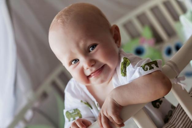 Jednoroczne niebieskookie dziecko w stylowym stroju patrzy na aparat z łóżeczka. małe i słodkie dziecko z uśmiechem siedzi w pokoju dziecięcym i czeka na mamę. koncepcja prawidłowego wychowania i dzieciństwa