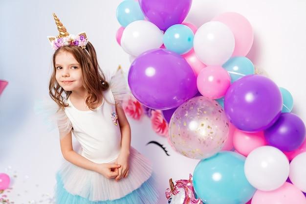 Jednorożec dziewczyna pozuje w pobliżu balonów. pomysł na dekorację przyjęcia urodzinowego w stylu jednorożca. jednorożecowa dekoracja na imprezową dziewczynę