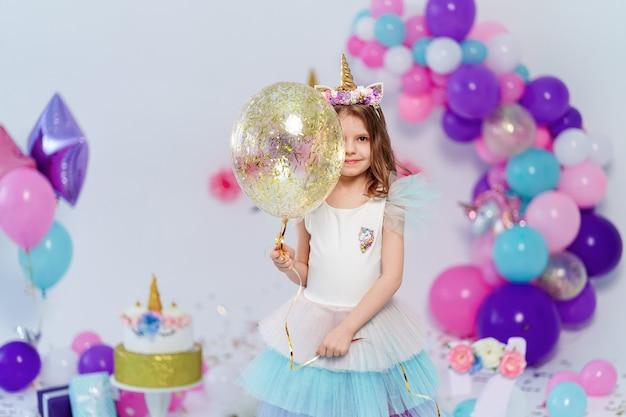 Jednorożec dziewczyna trzyma balon złoty konfetti powietrza. pomysł na dekorację przyjęcia urodzinowego w stylu jednorożca. jednorożecowa dekoracja na imprezową dziewczynę