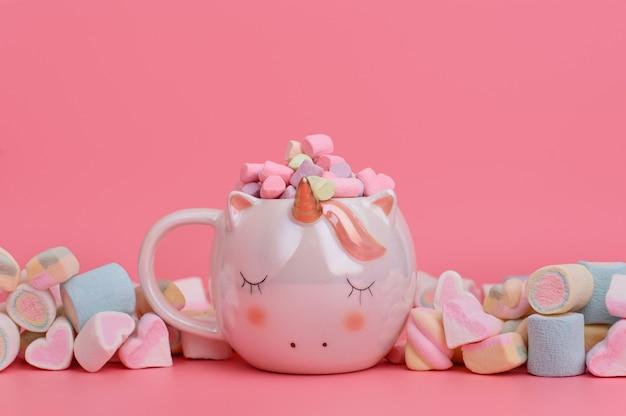 Jednorożec kubek z kolorowymi piankami na różowym tle. koncepcja słodyczy z miejscem na tekst. skopiuj miejsce na żywe różowe tło.
