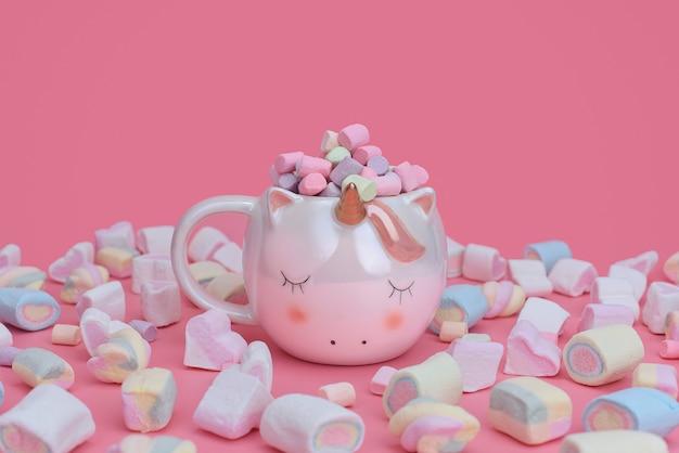 Jednorożec kubek z różnokolorowymi piankami rozrzuconymi po różowym tle. koncepcja słodyczy z miejscem na tekst.