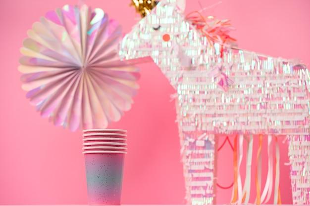 Jednorożec pinata na imprezę dla dzieci na różowym tle