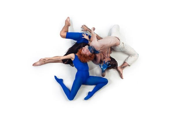 Jedność. grupa tancerzy nowoczesnych, art contemp dance, niebiesko-białe połączenie emocji. elastyczność i gracja w ruchu i akcji na białym tle studia. moda i uroda, koncepcja grafiki.