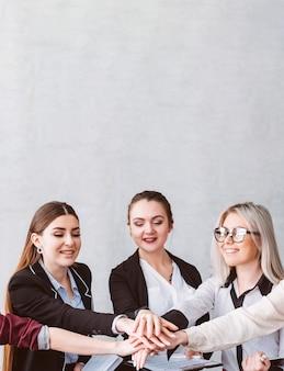 Jedność i współpraca. kobieca siła i wsparcie. zespół biznesu i solidarność kobiet. uśmiechnięci współpracownicy, składając ręce.