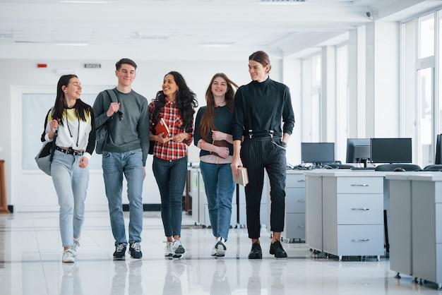 Jedność ludzi. grupa młodych pracowników spacerująca po biurze w czasie przerwy