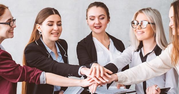 Jedność współpracy i wsparcie. kobieca moc. udane biznes panie składanie rąk. moment budowania zespołu kobiet