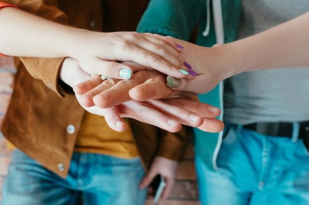 Jedność zespołu. przyjaciele koledzy kładą ręce razem. wolność kultury młodzieżowej.