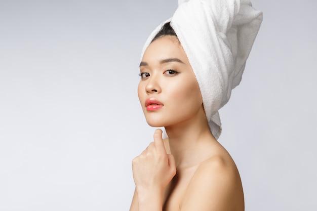 Jednostronny portret azjatyckiej pięknej uśmiechniętej dziewczyny z krótkimi włosami pokazując jej zdrową skórę