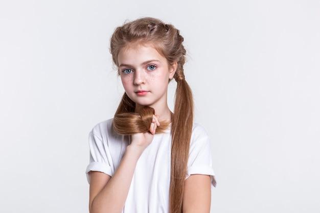 Jedwabiście jasne włosy. poważna urocza długowłosa dama zbiera włosy w pięść, mając na sobie zwykły biały t-shirt