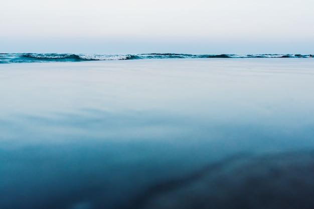 Jedwabiście spokojny woda tło z falami w tle i spokojne morze.