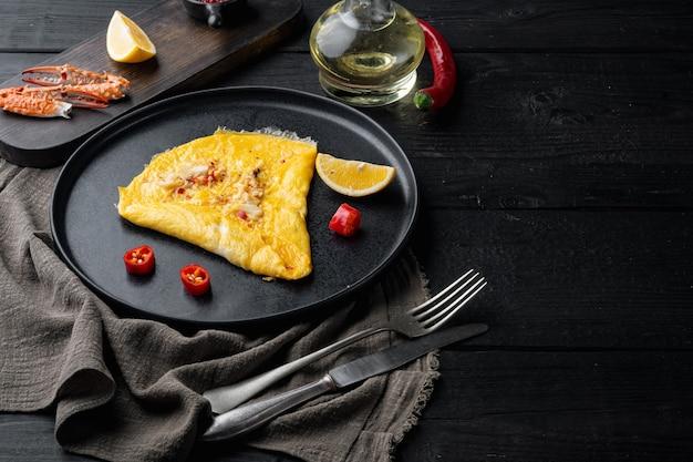 Jedwabisty omlet z krabem chili, na talerzu, na tle czarny drewniany stół