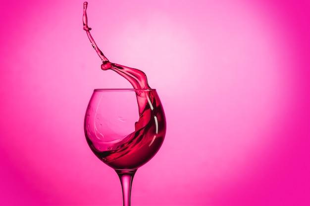 Jedyny kieliszek do wina z czerwonym winem na tle czerwonego studia
